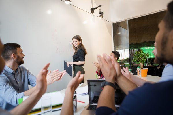 Picture of business people sitting round table and clapping their hands. Businesswoman performing in board room in front of audience in office interior.