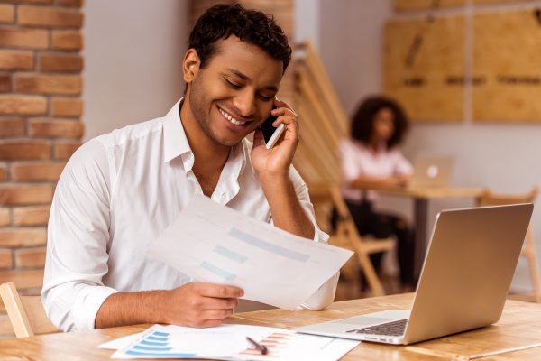 Young handsome Afro-American businessman in white shirt using laptop holding a graph talking on the phone and smiling while working in cafe