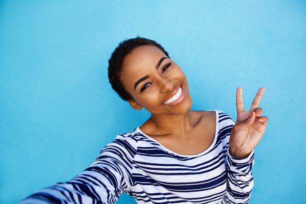 Portrait of cool young black woman taking selfie with peace hand sign